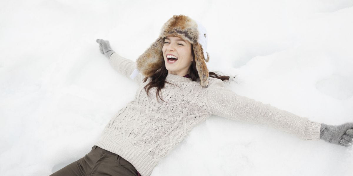 Enthusiastic woman making snow angel